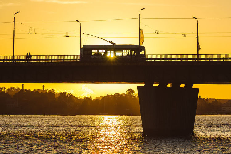 Riga Silhouettes Architecture Beauty In Nature Bridge Bridge - Man Made Structure Built Structure City Connection Daugava Day Illuminated Nature Nikon D750 Outdoors River River View Scenics Silhouette Silhouettes Sky Sunset Suspension Bridge Transportation Transportation Trolley Water