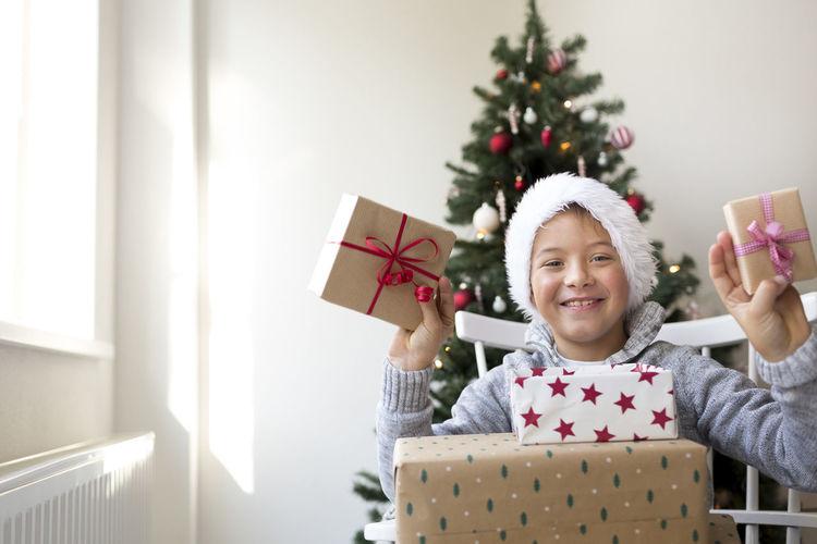 Portrait of happy boy holding gift box sitting against christmas tree