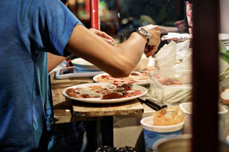 Midsection Of Vendor Preparing Food At Concession Stand