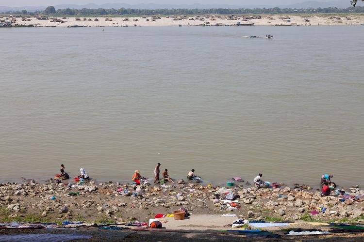 People washing clothes at riverbank