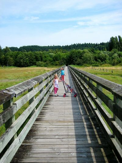 Full Length Of Girl With Sister And Baby Carriage Standing Amidst Field On Boardwalk