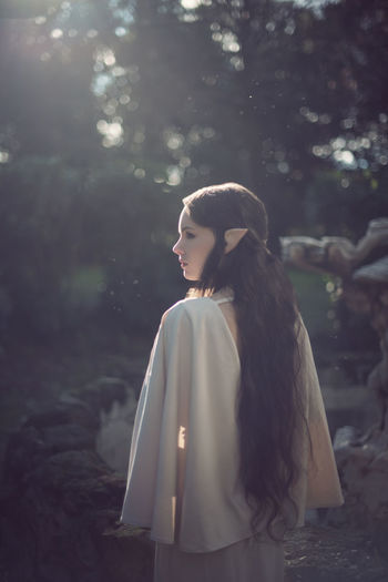 Thoughtful fairy elf young woman standing at park