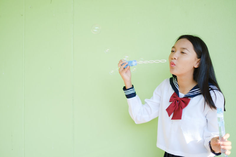 Full length of woman holding bubbles against wall