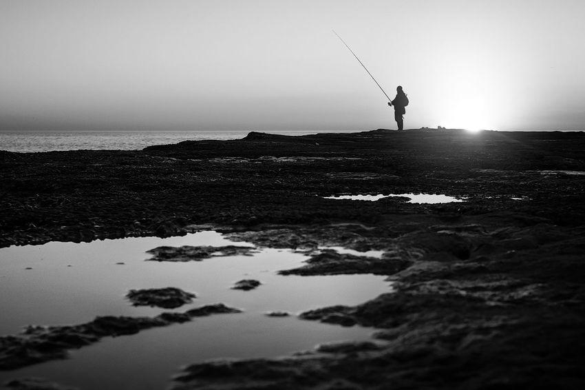 Lisbon,PT Lisbon - Portugal Lisbon Lisboa Beach Blackandwhite Black And White Blackandwhite Photography Silhouette Fisherman Water Rocks Reflection Monochrome Monochrome Photography