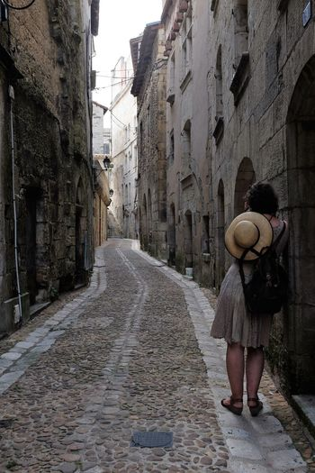 Rear View Of Woman Standing By Building In Alley