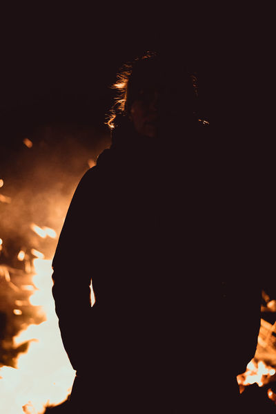 Fireplace Silhouette Adult Bonfire Burning Fire Fire - Natural Phenomenon Headshot Illuminated Leisure Activity Lifestyles Men Nature Night Nightlife One Person Portrait Real People Silhouette Standing Waist Up Young Adult Young Men