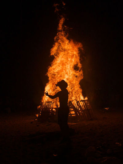 Man standing against fire at night