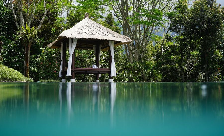A typical Balinese Gazebo by a swimming pool. Bali Balinese Garden Calmness Gazebo Architecture Calm Water Day Garden Lake Nature No People Outdoors Pool Reflection Swimming Pool Tree Water Waterfront