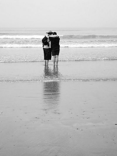 Rear view of couple standing on beach