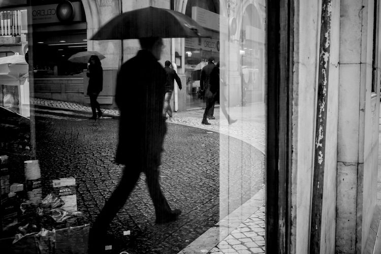Man with umbrella walking on footpath reflecting in glass window