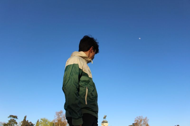 Low angle view of man standing against clear blue sky
