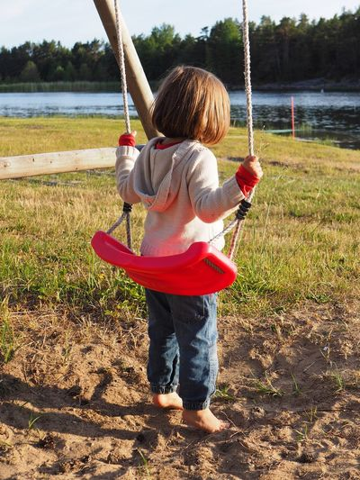 Childhood Child Water Full Length One Person Real People Leisure Activity Nature Holding Day Lake Casual Clothing Rear View Swing Lifestyles Plant Outdoors Innocence Girl Girls Red Red Color barefoot Sea View Cardigan Sand Meadow