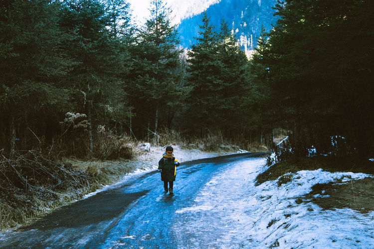 Boy Walking On Road In Forest During Winter