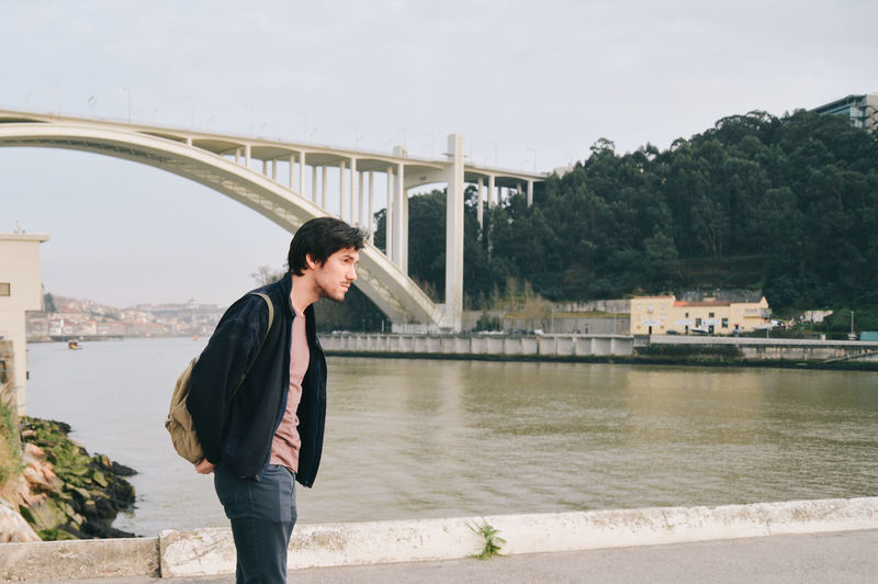 Man looking away while standing against bridge