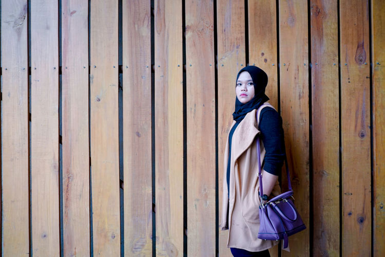 Portrait of woman standing against wooden wall