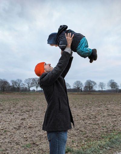 Side View Of Playful Father Lifting Daughter On Field During Winter