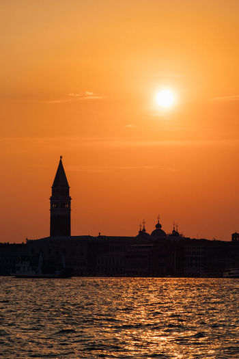 Grand canal by silhouette church of san giorgio maggiore against sky during sunset