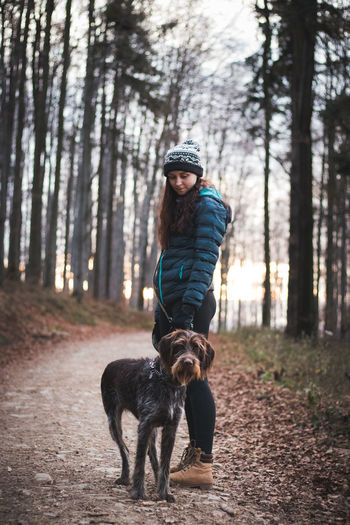 Full length of woman with dog in forest
