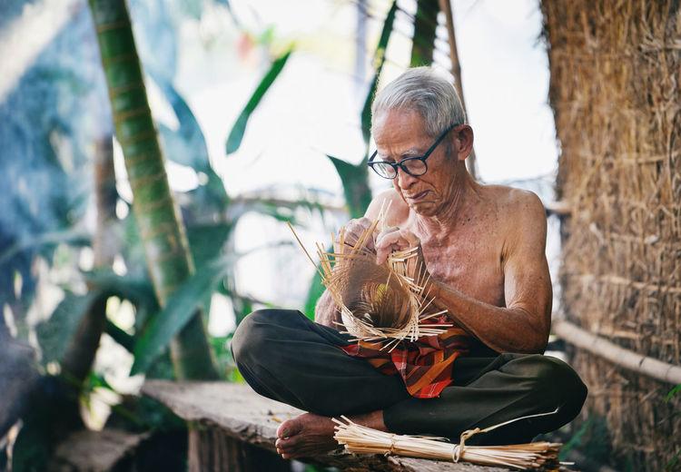 Senior man making craft product while sitting outdoors