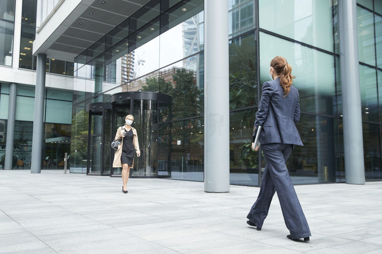 Full length of young woman walking against building in city