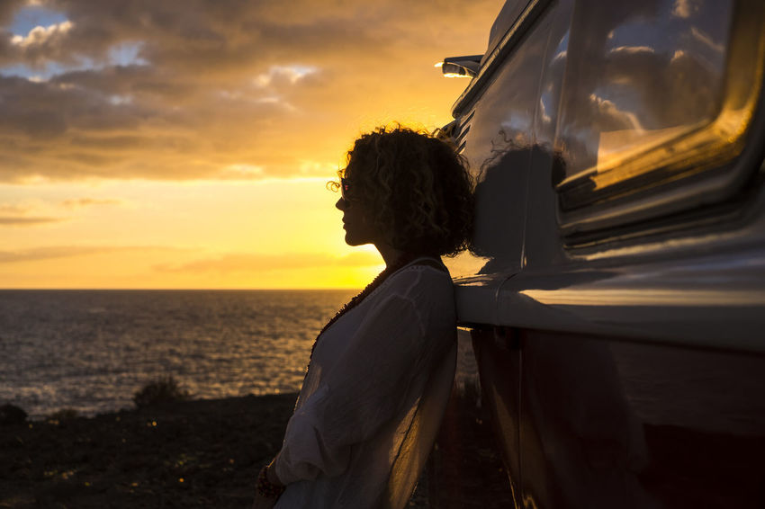 beautiful woman with blonde and curly hair traveling in vintage car Beauty In Nature Cloud - Sky Day Horizon Over Water Leisure Activity Lifestyles Nature One Person Outdoors People Real People Rear View Relaxed Moments Scenics Sea Sky Standing Suggestive Place Sunset Tranquillity Water Young Woman
