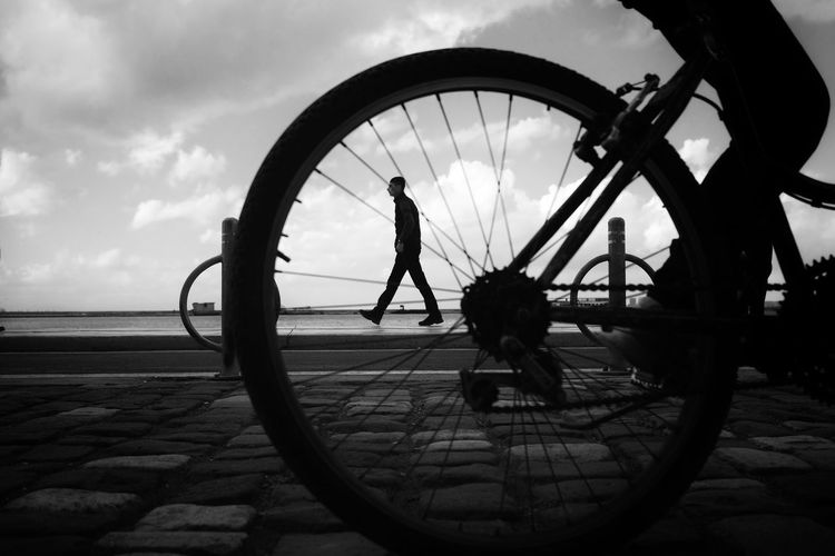 Silhouette people riding bicycle by sea against sky