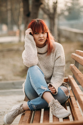 One Person Sitting Casual Clothing Young Women Young Adult Full Length Real People Lifestyles Women Leisure Activity Adult Front View Clothing Day Hairstyle Redhead Wood - Material Seat Beautiful Woman Outdoors Bangs Jeans Scarf Warm Clothing