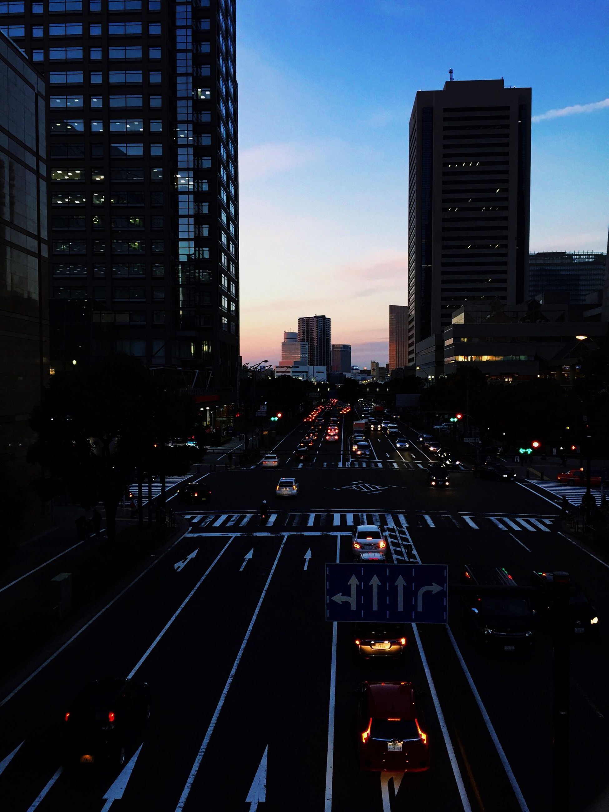 city, building exterior, architecture, built structure, transportation, skyscraper, office building, illuminated, tall - high, modern, railroad track, sky, city life, tower, cityscape, sunset, dusk, high angle view, road, traffic