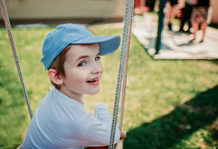 Portrait of cute boy sitting on swing