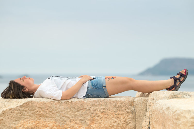 Girl with Tattoo Lying on the Ancient Amphitheater in Kaş. Ancient Ancient Architecture Ancient Ruins 43 Golden Moments Casual Clothing Natural Light Portrait Eyes Closed  Girl Girlswithtattoos Kas The Essence Of Summer Lifestyles Lying Down Portrait Portrait Of A Woman Relaxation Ruins Sky The OO Mission Fine Art Photography Tattoo Tattooed Tattoos The Portraitist - 2016 EyeEm Awards Original Experiences