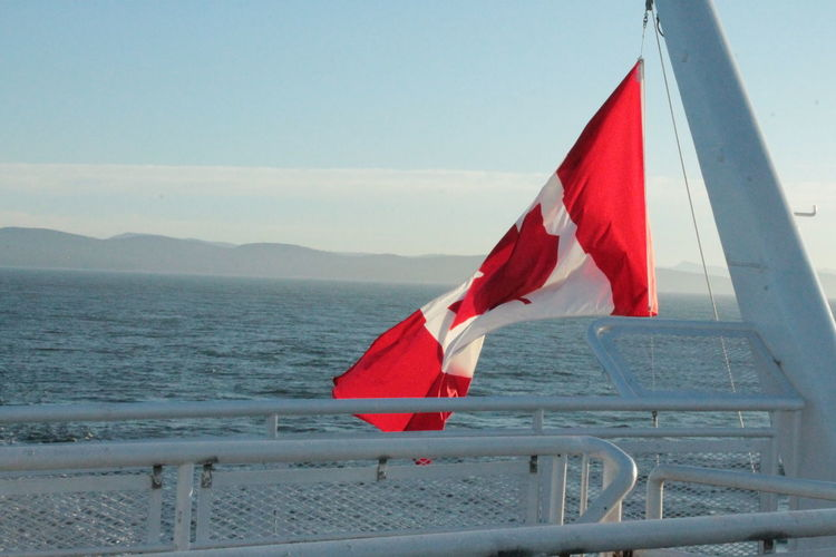Views Beauty In Nature Canada Flag Day Ferry Views Flag Fog Landscape Mist Mountains Nature No People Ocean Outdoors Patriotism Red Sky Water