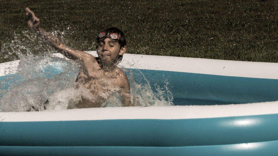 Shirtless Boy Enjoying In Wading Pool At Backyard