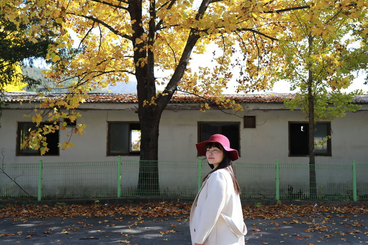 Full length of girl standing by tree during autumn