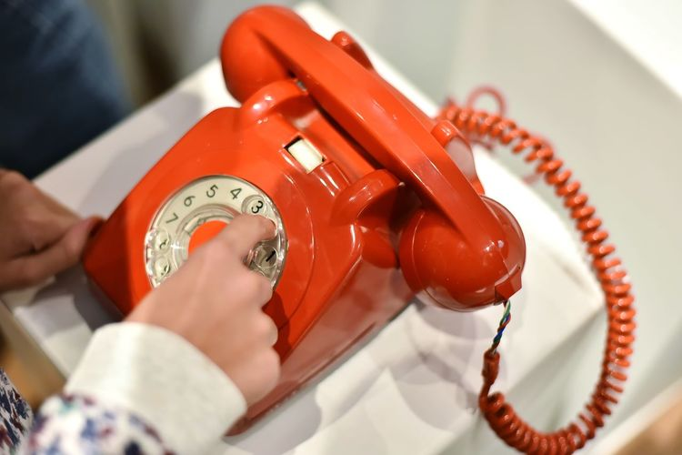 Cropped hand dialling on telephone