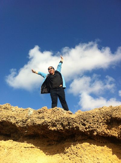 Woman With Hands Raised Against Blue Sky And Clouds