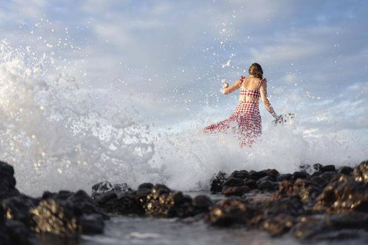 Woman splashing water in sea