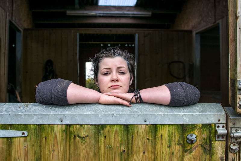 Young farmhand taking a break from working in the stables Arms Crossed Barn Break Time Candid Centred Cute Door Equine Farm Farm Hand Girl Helensburgh Leaning Lifestyles Lock Looking At Camera Portrait Posing Scotland Scottish Stable Woman Wooden Work Plave Young Adult