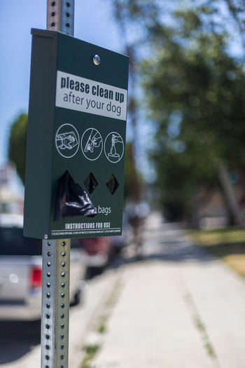 dog poop bag dispenser Bags Close-up Communication Convenience Day Dispenser Dog Poop Bag Dispenser Focus On Foreground No People Outdoors Park Sidewalk Sky Street Text Tree