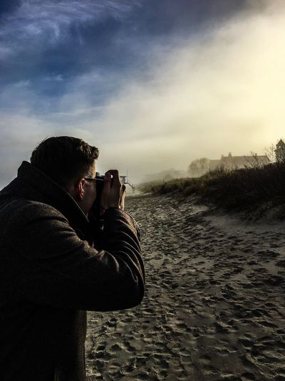Man Photographing While Standing On Sand Against Cloudy Sky