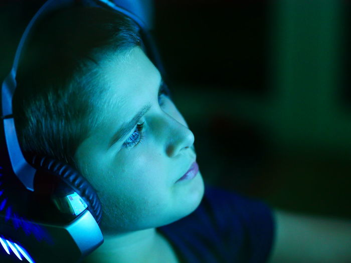 Close-up of boy wearing headphones sitting at home
