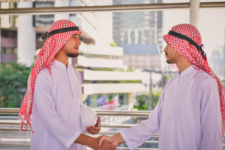 Side view of smiling businessman shaking hands with colleague on elevated road in city