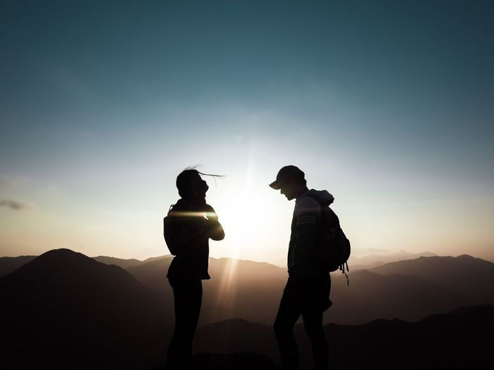 Silhouette of two men against sky