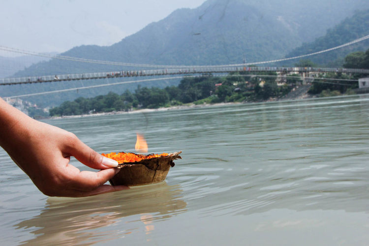 Close-up of person holding diya on water surface
