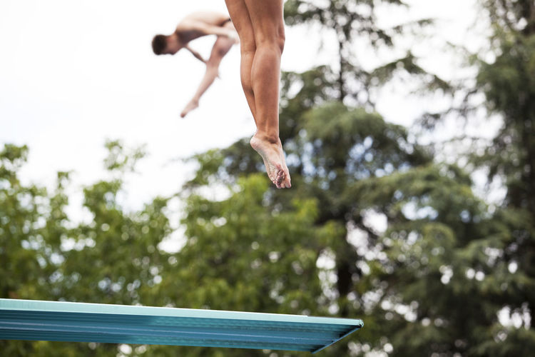 Jumping from a springboard Diving Fly Free Freedom Fun In The Air Jump Swimming Acrobatics  Diver Flexibility Flying Height High In The Air Jumping Legs Mid-air Motion Sport Sports Springboard Springboard Diver Springboard Diving Strenght Swimmer