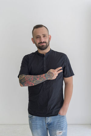 young businessman with tattoo, black t-shirt, beard and black hair, and with a white background, young guy with beard and black hair outlined on a white background Black Hair Businessman Businessmanagement Front View Manager Professional Tattoo White Background Young Guy