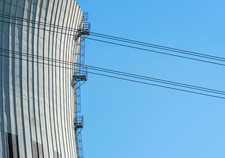 Low angle view of cool tower with cables against clear blue sky