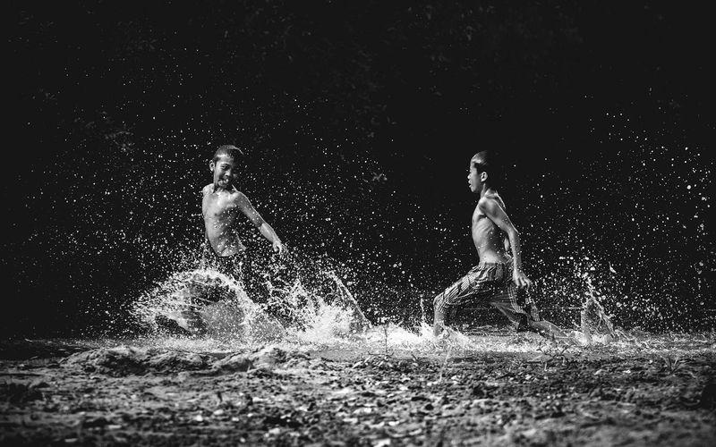 Boys playing in lake at night