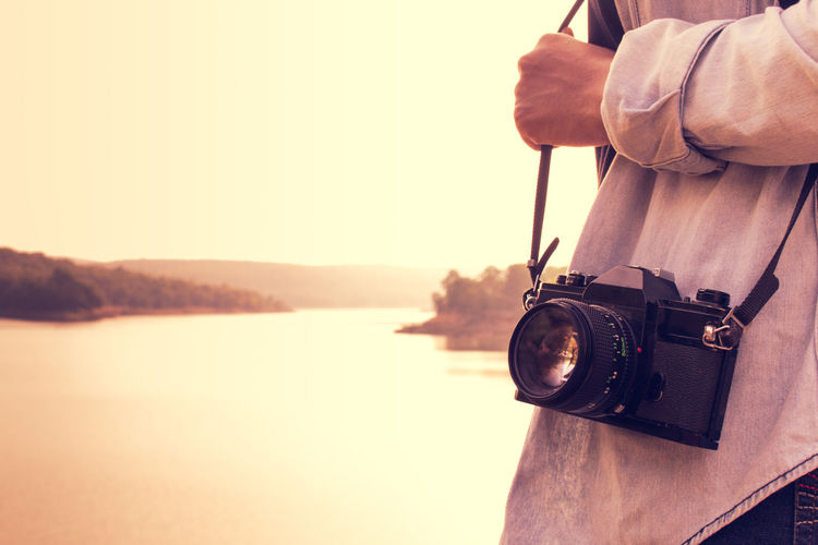 Midsection Of Woman With Camera Standing Against River
