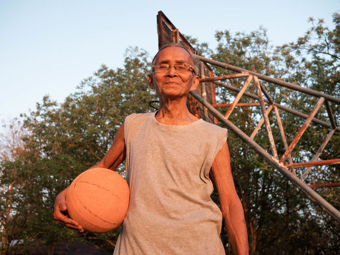 Portrait of man holding basketball while standing outdoors
