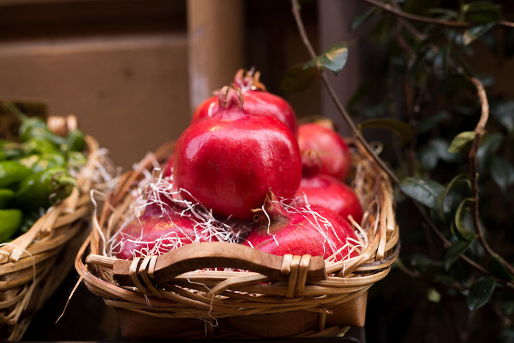 Basket of pomegranates in the greengrocery